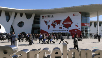 People walk next to the Mobile World Congress banner in Barcelona